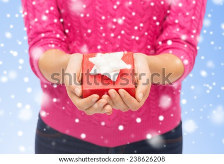 christmas, holidays and people concept - close up of woman in pink sweater holding small red gift box over blue background with snow over blue background with snow - stock photo