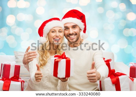 christmas, holidays and people concept - happy couple in santa hats with gift boxes sitting on sofa and showing thumbs up at home over blue lights background