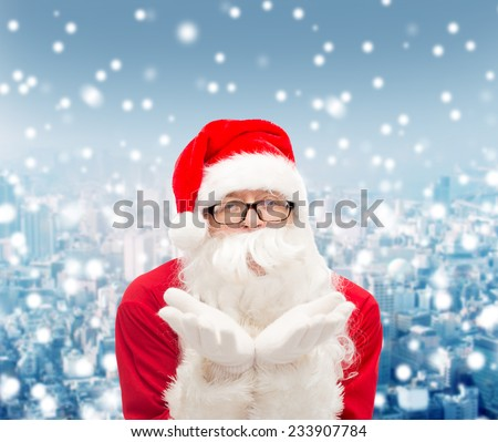 christmas, holidays and people concept - man in costume of santa claus blowing on palms over snowy city background