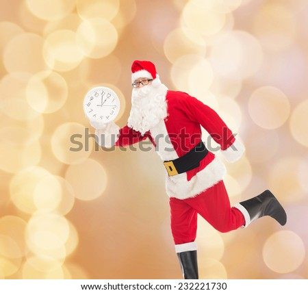 christmas, holidays and people concept - man in costume of santa claus running with clock showing twelve over beige lights background