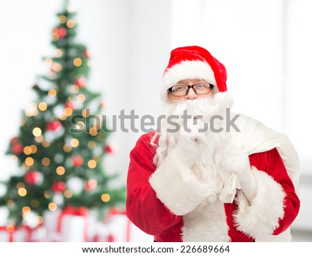christmas, holidays and people concept - man in costume of santa claus with bag making hush gesture over living room with tree - stock photo