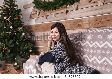 Christmas, holidays and people concept - young pretty girl laying on a cosy sofa in Christmas time - stock photo