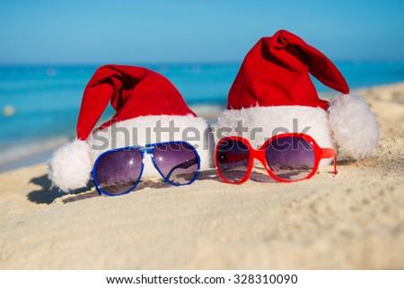 Christmas holidays and Romantic New Year at Sea. Santa hats and sunglasses on sandy beach - stock photo
