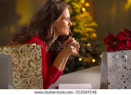 Christmas holidays are a time of gift-giving. Todo list can make Christmas season easy and save time for more fun.Happy young woman among shopping bags with pen and notebook thinking what's left to do - stock photo