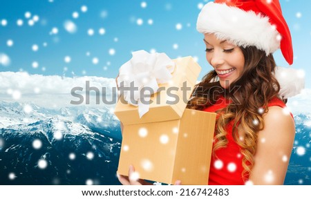 christmas, holidays, celebration and people concept - smiling woman in red dress with gift box over blue snowy background