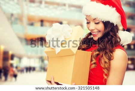 christmas, holidays, celebration and people concept - smiling woman in red dress with gift box over shopping center background - stock photo