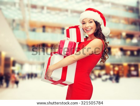 christmas, holidays, celebration and people concept - smiling woman in red dress with gift boxes over shopping center background - stock photo