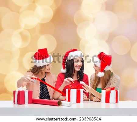 christmas, holidays, celebration, decoration and people concept - smiling women in santa helper hats with decorating paper and gift boxes over beige lights background