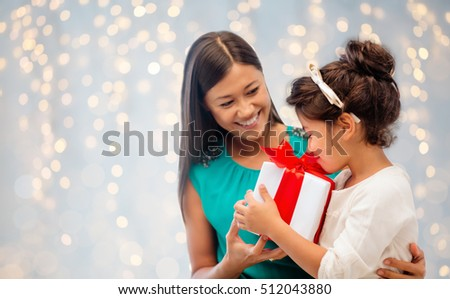 christmas, holidays, celebration, family and people concept - happy mother and child girl with gift box over blue lights background