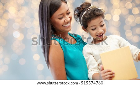 christmas, holidays, celebration, family and people concept - happy mother and child girl with gift box over lights background
