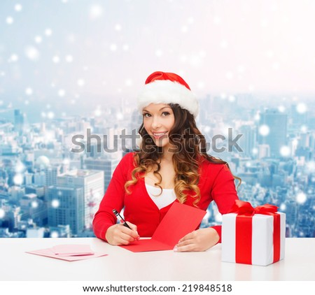 christmas, holidays, celebration, greeting and people concept - smiling woman in santa helper hat with gift box writing letter or sending post card over snowy city background - stock photo