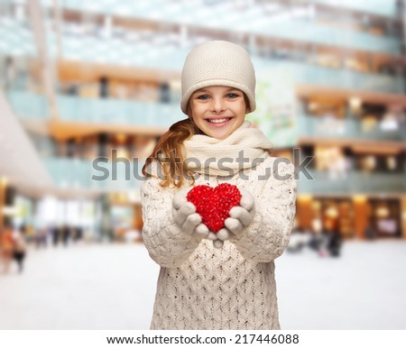 christmas, holidays, childhood, presents and people concept - dreaming girl in winter clothes with red heart over blue lights background - stock photo