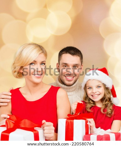 christmas, holidays,  family and people concept - happy mother, father and little girl in santa helper hat with gift boxes over beige lights background