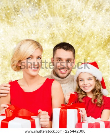 christmas, holidays,  family and people concept - happy mother, father and little girl in santa helper hat with gift boxes over yellow lights background