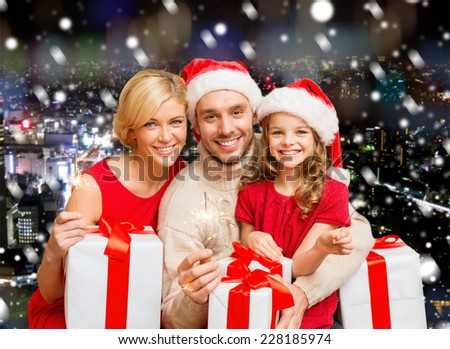 christmas, holidays, family and people concept - happy mother, father and little girl in santa helper hats with gift boxes and sparklers over snowy night city background