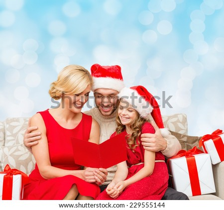 christmas, holidays,  family and people concept - happy mother, father and little girl in santa helper hats with gift boxes reading geeting card over blue lights background