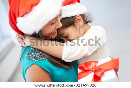 christmas, holidays, family, childhood and people concept - happy mother and little girl in santa hats cuddling at home - stock photo