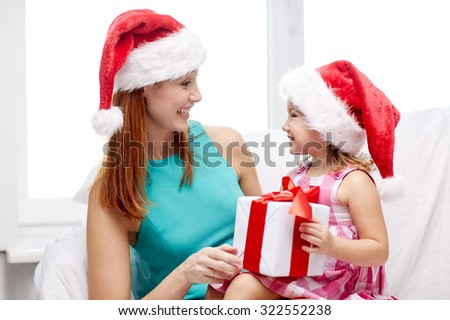 christmas, holidays, family, childhood and people concept - happy mother and little girl in santa hats with gift box at home - stock photo