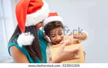 christmas, holidays, family, childhood and people concept - happy mother and little girl in santa hats opening gift box at home - stock photo
