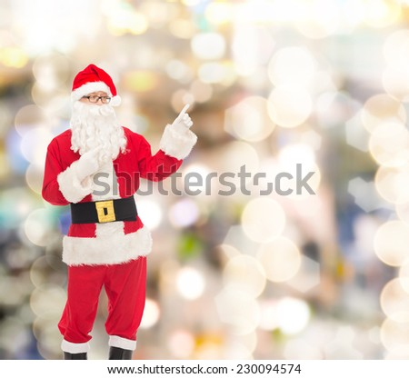 christmas, holidays, gesture and people concept - man in costume of santa claus pointing fingers over lights background - stock photo