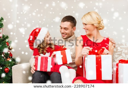 christmas, holidays, happiness and people concept - smiling family in santa helper hats with many gift boxes at home
