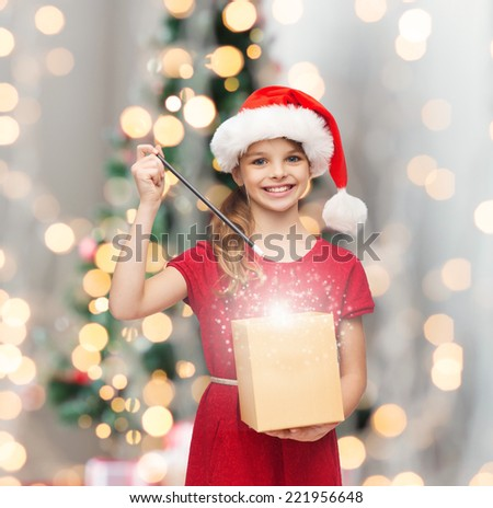 christmas, holidays, happiness and people concept - smiling girl in santa helper hat with gift box and magic wand over living room and christmas tree background - stock photo