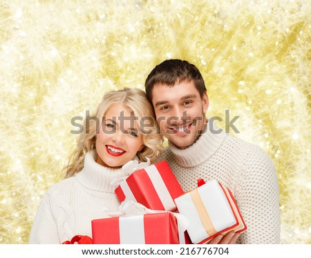 christmas, holidays, happiness and people concept - smiling man and woman with presents over yellow lights background