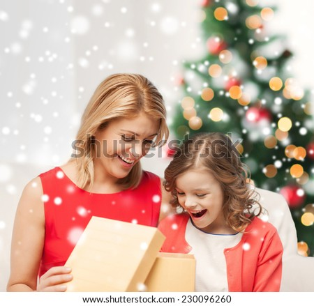 christmas, holidays, people and family concept - smiling mother and daughter opening gift box and getting surprised at home - stock photo