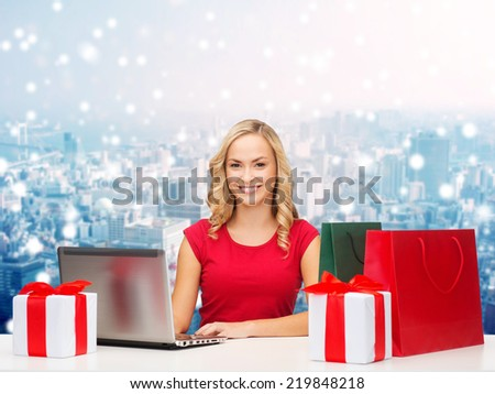 christmas, holidays, technology, advertising and people concept - smiling woman in red blank shirt with shopping bags, gifts and laptop computer over snowy city background