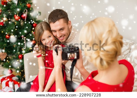 christmas, holidays, technology and people concept - happy family with digital camera taking photo at home - stock photo