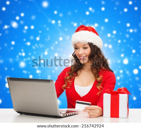 christmas, holidays, technology and shopping concept - smiling woman in santa helper hat with gift box, credit card and laptop computer over blue snowing background - stock photo