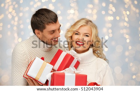 christmas, holidays, valentine's day, celebration and people concept - smiling man and woman with presents over lights background