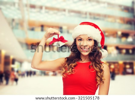 christmas, holidays, winter, happiness and people concept - smiling woman in santa helper hat with jingle bells over shopping center background - stock photo