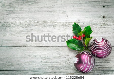 Christmas holly and pretty purple baubles with a spiral pattern on rustic wooden white painted boards with woodgrain texture and plenty of copyspace - stock photo