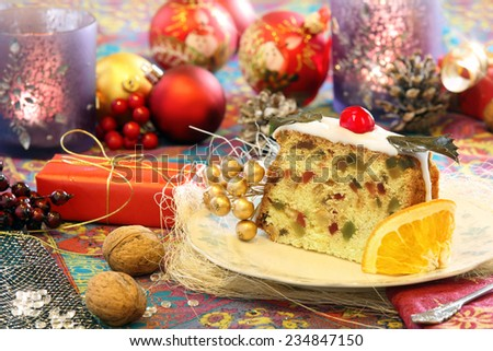 Christmas holly fruitcake on the decorated table - stock photo