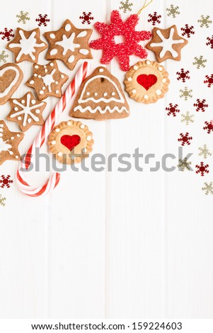 Christmas homemade gingerbread cookies and decoration over white wooden board