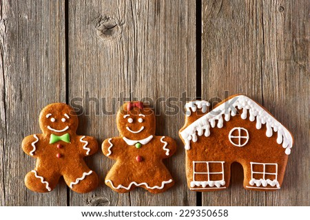 Christmas homemade gingerbread couple and house on wooden table - stock photo