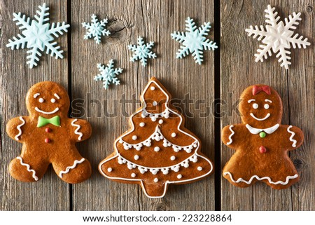 Christmas homemade gingerbread couple and tree on wooden table - stock photo