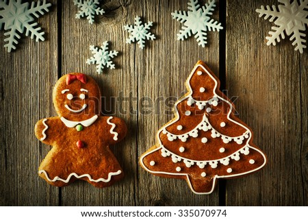 Christmas homemade gingerbread girl and tree on wooden table - stock photo