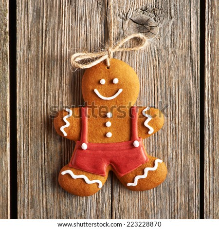 Christmas homemade gingerbread man over wooden background - stock photo