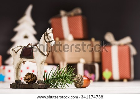 Christmas horse with spruce branches and fir cone closeup on dark background with gifts - stock photo