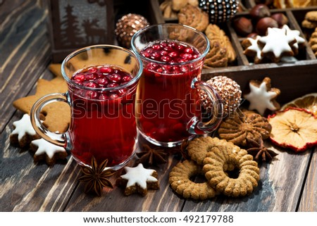 Christmas hot cranberry tea and cookies on dark background, closeup, horizontal