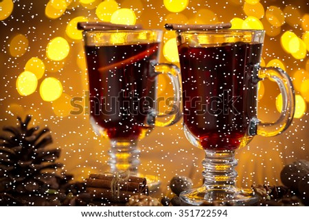 Christmas hot mulled wine with spices on a wooden table with snow. The idea for creating greeting cards