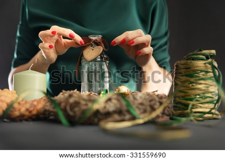 Christmas house decoration. Christmas. Woman packs a Christmas gift and decorating the house with Christmas decorations  - stock photo