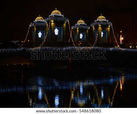 Christmas illumination on a city bridge with reflection in water.