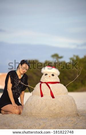 Christmas in Florida - girl and sandman on the beach - stock photo