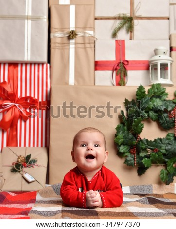 Christmas infant baby child lying rustic craft decoration gift presents boxes background. New Year 2016 holiday concept  - stock photo