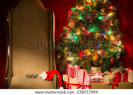 Christmas interior with illuminated Christmas tree and chair. Gifts at the Christmas tree. Horizontal image.
