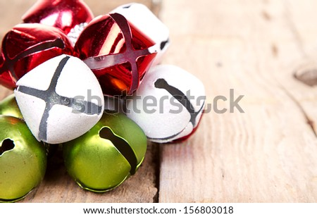 Christmas jingle bells on a rustic wooden plank - stock photo