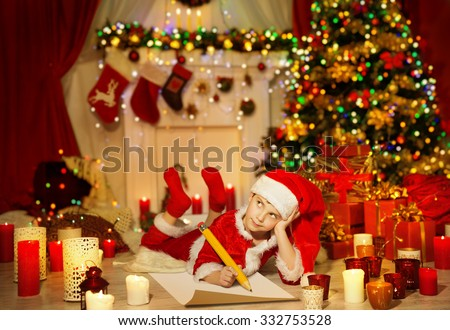 Christmas Kid Write Wish List, Child in Santa Claus Hat Writing Letter, Boy in Holiday Room lying under Christmas Tree - stock photo